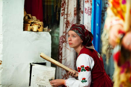 Belarus, Gomel region, Mihalki village, September 23, 2017. Reconstruction of the ancient ceremony of the wedding of the fireplace.A woman in Belarusian clothes near an old stove. Melt the fire in the oven.