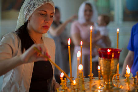 Belarus, the city of Gomil, June 20, 2019. City church.Women lights a church candle.