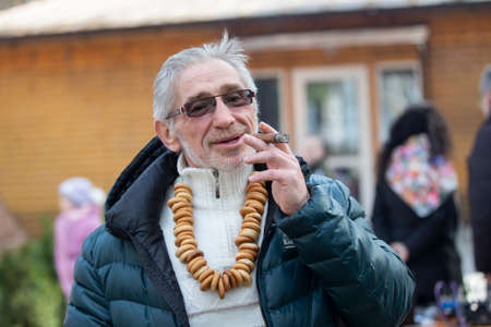 Belarus, the city of Gomel, March 09, 2019.Belarus, the city of Gomel, March 09, 2019.Maslenitsa.A man with a cigar at the festival Maslenitsa.