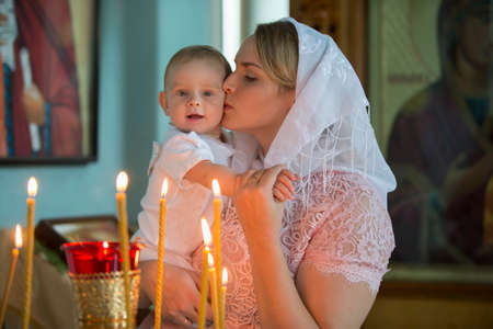 Belarus, the city of Gomil, June 20, 2019. City church.Belarus, the city of Gomil, June 20, 2019. City church. Orthodox baptism. Mother and child in a church by candlelight. Woman with a baby in the temple.