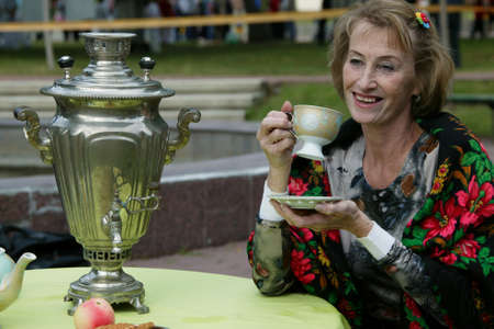 Belarus, the city of Gomil, November 21, 2015. The streets of the town. Russian woman drinks tea from a samovar.