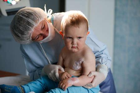 To a little boy, a nurse heals a burn.