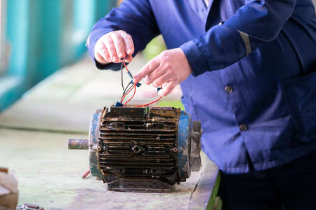 Worker's hands make an old electric motor. Stockfoto