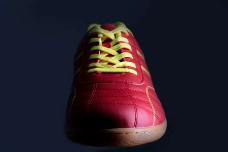 Red sneaker on a black background. Sport shoes