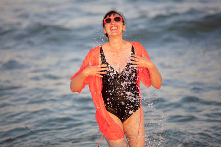 Happy woman at the sea with splashes
