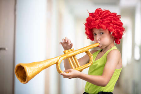A child in a bright wig plays the trumpet. Funny boy with a toy musical instrument. Future artist