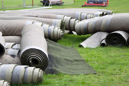 Old artificial lawn twisted into rolls