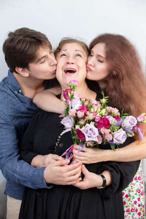 Holiday at the woman. Elderly woman with a bouquet of flowers surrounded by children. Boyfriend and girlfriend kiss grandmother. Children congratulate mom. Happy adult woman accepts congratulations.