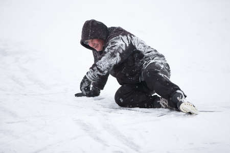 The man fell on skates in the snow. An elderly man learns to ride a hockey skate