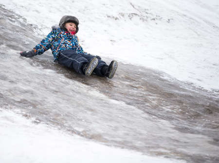 Child rides on an ice slide. Cheerful boy in the winter.