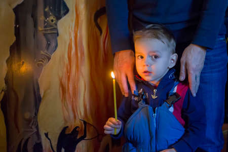 Belarus, the city of Gomel, Prudkovskaya church. January 19, 2019 The celebration of the baptism of Jesus.A child with a candle in the church