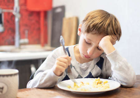 The child does not want to eat. Poor appetite. A boy sits over a plate with tears Stock Photo