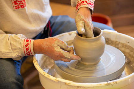 The hands of the master make a pot of clay.
