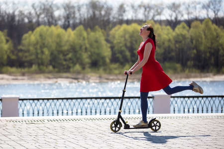 An adult woman is riding a scooter on the street. Active middle-aged woman on a walk.
