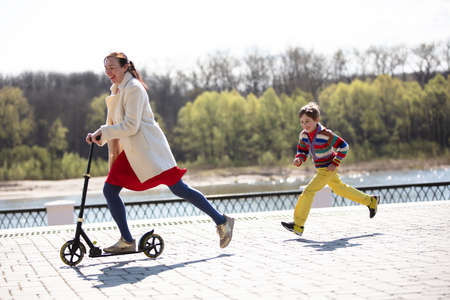 A woman is riding a scooter and her son runs after her. Mom and son on a walk in the park. Фото со стока