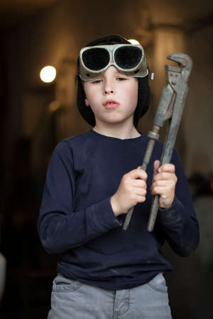 Boy in welding goggles with a wrench Фото со стока