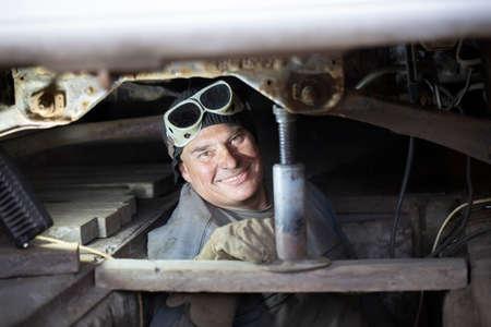 A male auto mechanic repairs a car in a garage.