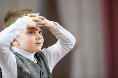 A preschooler boy thinks. The child thought about it