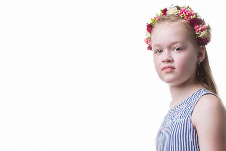 Beautiful teenager girl in a wreath of flowers on a white background.