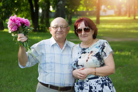 Happy elderly couple with a bouquet of flowers. Фото со стока