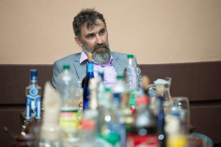 A man with a beard on the background of alcohol bottles on the table.