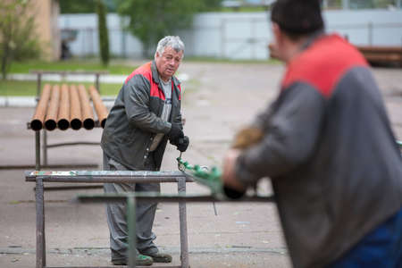 Factory workers are folding metal pipes.Workers on the territory of the plant. Фото со стока