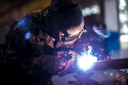Welder at work. Man in a protective mask. The welder makes seams on the metal. Sparks and smoke when welding.