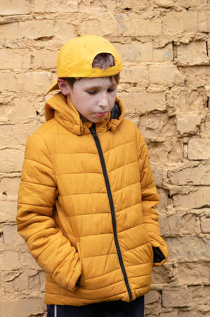 A child on the street. A overweight boy is standing against a brick wall in yellow clothes and a baseball cap. Stock Photo