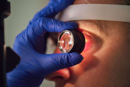 An ophthalmologist checks the fundus of the patient.