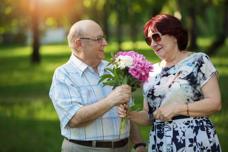 Happy elderly couple with flowers. Handsome man and woman senior citizens. Husband and wife of old age for a walk.