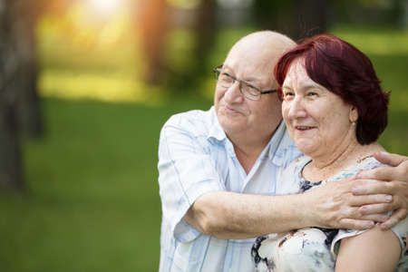 Happy elderly couple on a walk. Handsome man and woman senior citizens. Husband and wife of old age against the background of nature.
