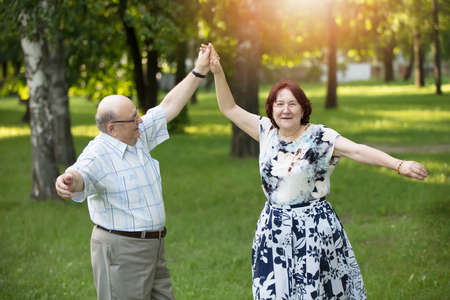 Happy elderly couple dancing. Handsome man and woman senior citizens. Husband and wife of old age for a walk.