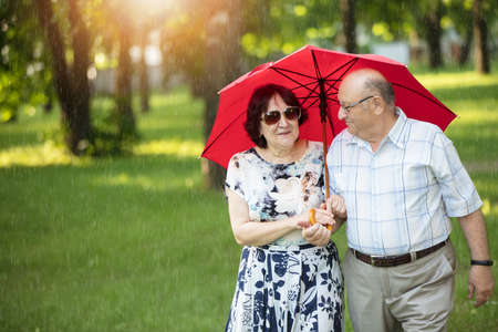 Happy elderly couple with umbrella. Handsome man and woman senior citizens. Husband and wife of old age for a walk. Фото со стока