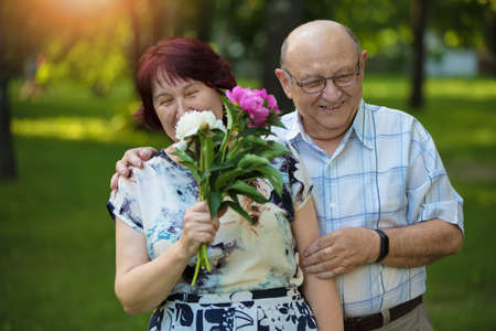 Happy elderly couple with flowers. Handsome man and woman senior citizens. Husband and wife of old age in the park. Фото со стока