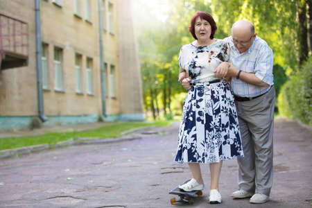 Happy elderly couple with a skateboard. Handsome man and woman senior citizens. Husband and wife of old age for a walk in the city.