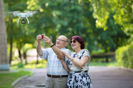 Happy elderly couple on a walk. Elderly husband and wife with a drone. Loving spouses in adulthood.