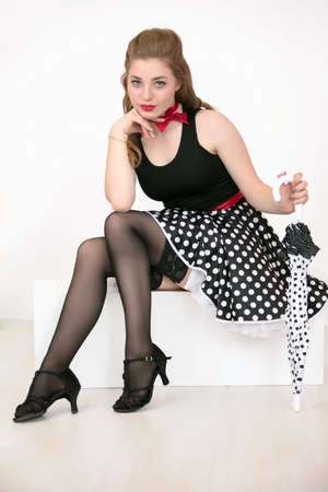 Beautiful retro girl. Woman dressed in the style of the fifties posing with an umbrella.