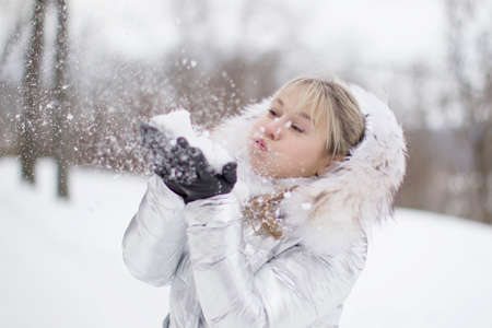 Woman in a white jacket blowing snow flakes