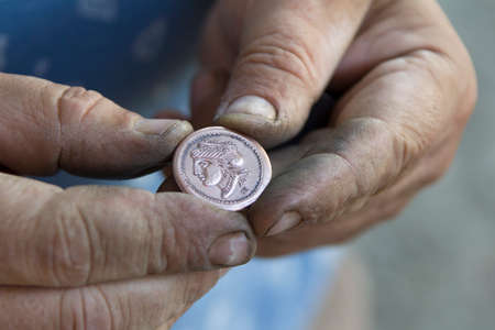 Hands hold ancient coin