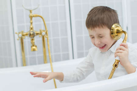 Baby in the bathroom in clothes.The boy sits in the bath and plays the phone.Talking on the phone Standard-Bild