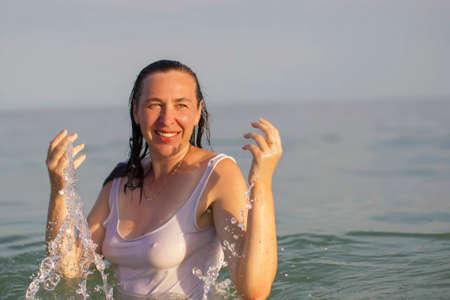 Elderly woman in sea water. Middle-aged woman bathing in the ocean.