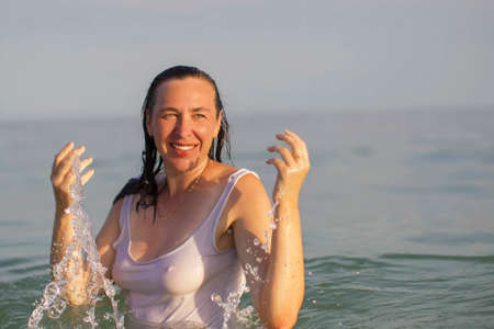 Elderly woman in sea water. Middle-aged woman bathing in the ocean.