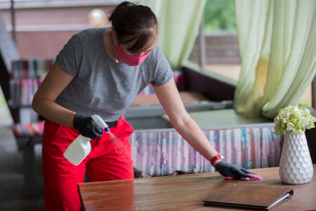 Waiter wearing protective face mask while disinfecting tables at outdoor cafe Stock fotó