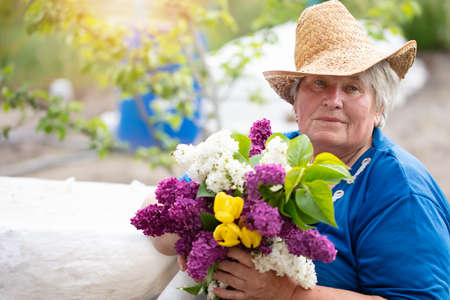 Gray-haired beautiful elderly woman with a bouquet of lilacs outdoors. Pensioner in the country.