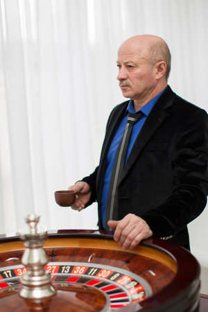 Elegant elderly man in a casino with a cup of coffee