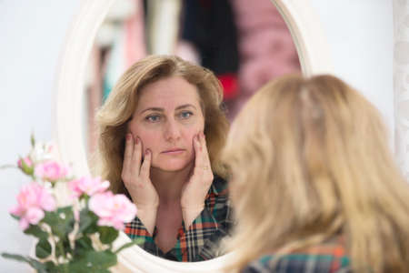 An elderly woman looks in the mirror at the wrinkles. Woman touches her aged face