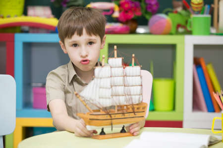 Boy playing with ship.Child with a toy sailboat