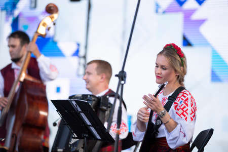 08/29/2020 Belarus, Lyaskovichi. Celebration in the city. Women in national Slavic dress plays the balalaika.