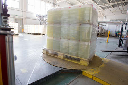 The machine for packing cellophane. Plastic jars wrapped in cellophane Banco de Imagens