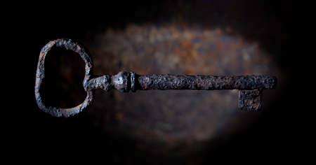 Rusty vintage key on a dark corrosion background Imagens